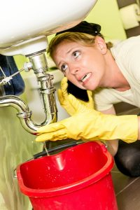 woman with rubber gloves on looking at leak under bathroom sink