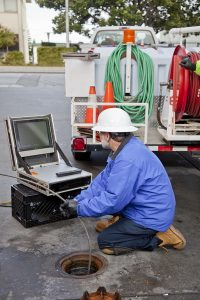 plumber-looking-at-screen-using-video-pipe-inspection