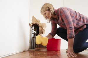 worried-homeowner-mopping-up-water-from-floor