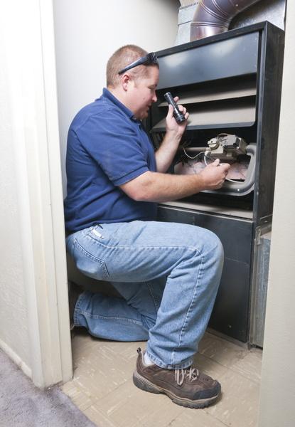 technician-looking-into-furnace