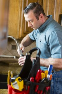 plumber-working-on-kitchen-sink-faucet