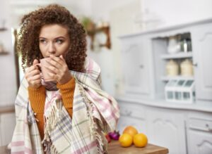 woman-huddled-with-blanket-drinking-from-mug